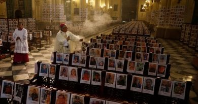 Powerful image of Archbishop  in cathedral surrounded by pictures of Coronavirus victims